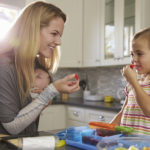 Mum and older daughter eating fruit, while baby sleeps in baby carrier